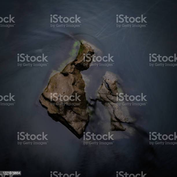Photo of Water Rushes Around Boulders in River