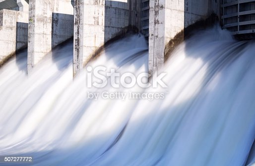 Water in long exposure rushing out of open gates of a hydro electric power station