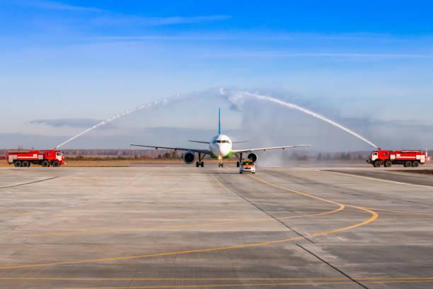Wassergruß per Feuerwehrauto am Flughafen für den ersten Besuch Passagierflugzeug. Das Flugzeug bewegt sich hinter dem Follow-me-Car – Foto