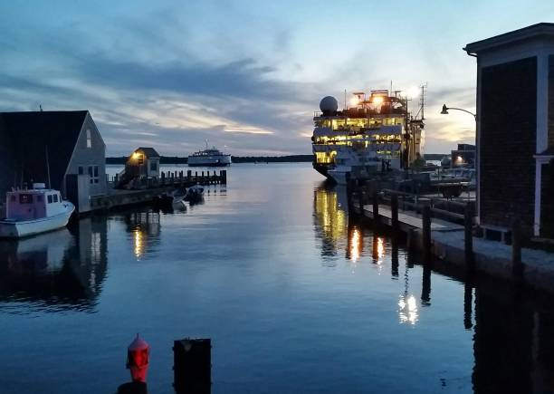 Water Scene at Dusk with Lighted Steamboat, a Pier and Boathouse stock photo