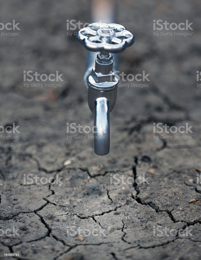 A water spigot over dry cracked soil of a drought stock photo