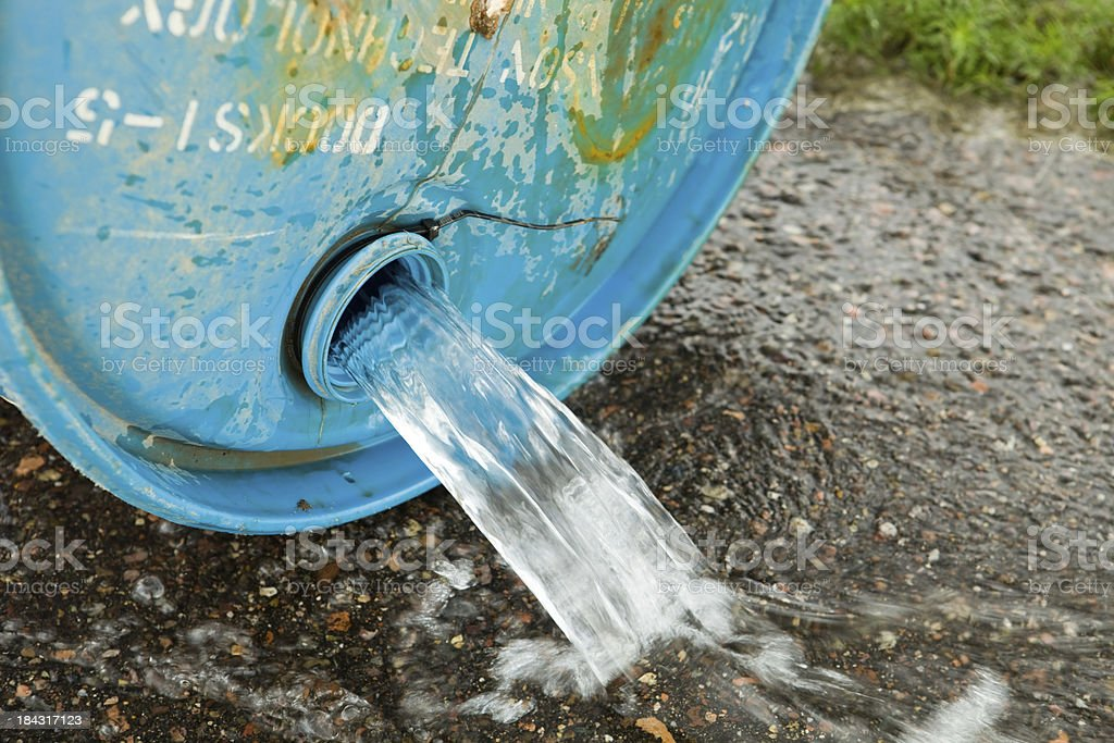 Water Spilling from a Barrel onto Asphalt stock photo