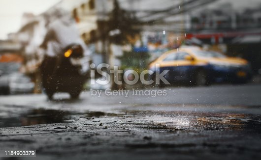 Water splash  (with  crown shape) during hard rain fall in the city with blurry cars as background .Selective focus.