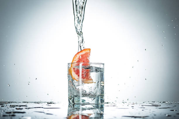 water splash in glass of gray color - grapefruit cocktail stock photos and pictures