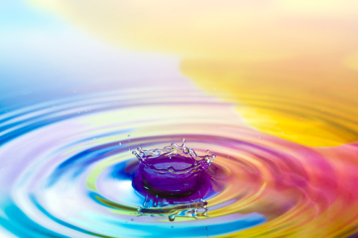 A waterdrop falling down into the rippled colored water.