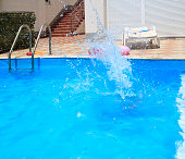 water splashes after the kid's jump into the pool