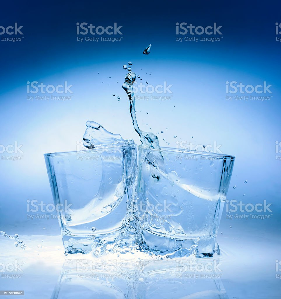 Water splashes in a glass with ice stock photo