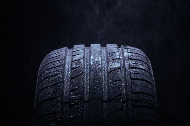 vatten stänk på ett nytt symmetriska däck under regnet - wheel black background bildbanksfoton och bilder