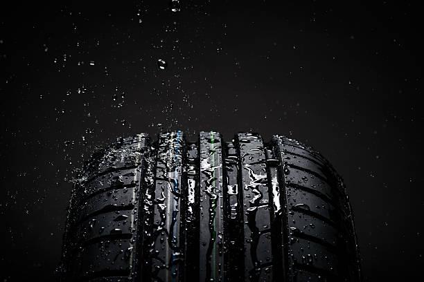 water splashing on a new symmetrical tire during the rain - wheel black background bildbanksfoton och bilder