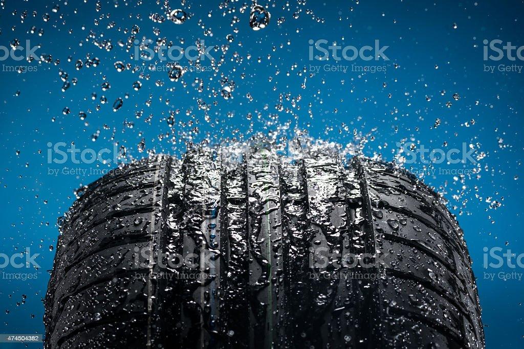 Wasser planschen auf eine neue Reifen vor blauem Hintergrund – Foto