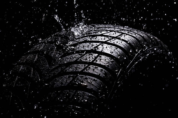 """Water splashing on a new tire during the rain """"Brand new, wet, high performance wet winter tire Goodyear UltraGrip. RainingSpace AdobeRGB More in"""" slow motion stock pictures, royalty-free photos & images"""