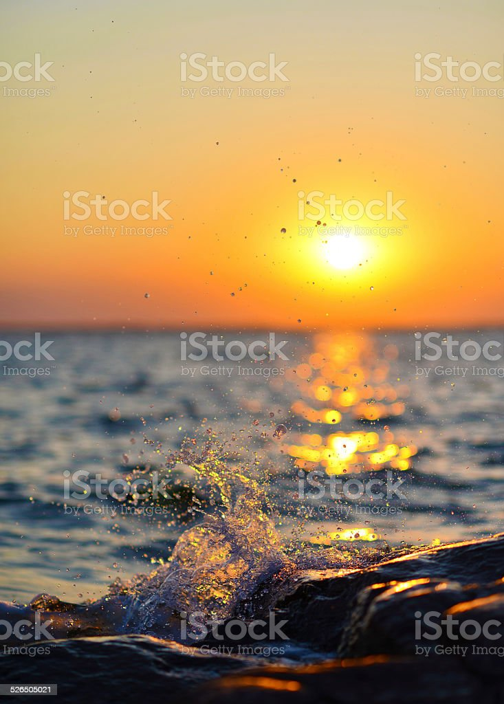 Water Splashing on Shore against Glittering Sunset stock photo