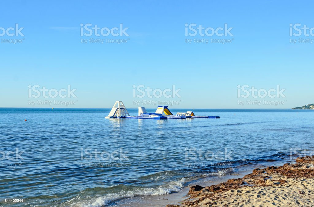 Water sport air slide on sea water near beach with sand stock photo