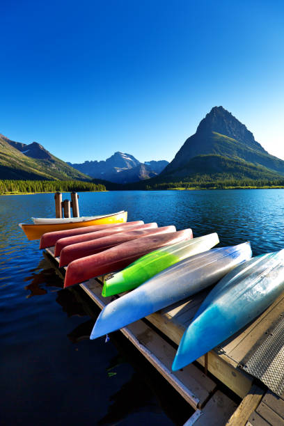 water sport kayaks, canoes at many glacier at glacier national park, montana usa - us glacier national park stock pictures, royalty-free photos & images