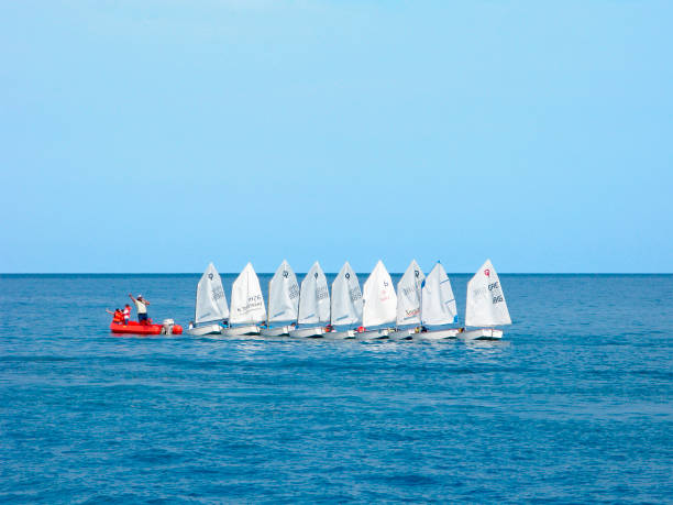 Water sport. Training of children on dinghies. Greece, Crete. Training of children on dinghies. Trainer on red dinghy. Junior yachtsmen on sailboats in a row in the open sea. sailing dinghy stock pictures, royalty-free photos & images