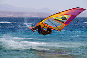 Eilat, Israel - April 12, 2019: Adventurous Man is enjoying water sports, Windsurfing, in the Red Sea during a sunny day.