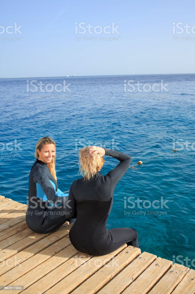 Water sports team. Pretty scuba diver, two attractive, vital, mature women. ready to go scuba diving or snorkeling. Dressed in a wet suit. Long blonde hair, beautiful blue eyes. Sporting women. Beautiful blue sea in the background. royalty-free stock photo