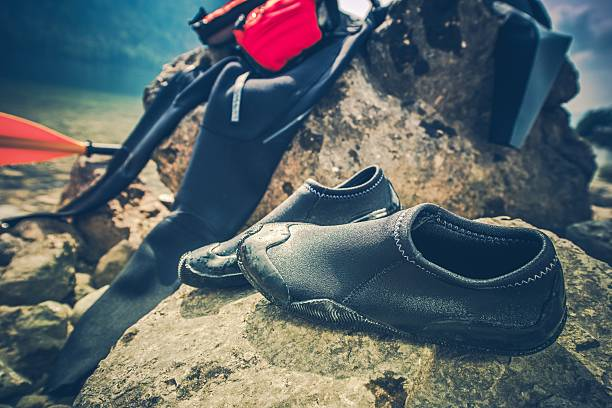 Water Sports Wetsuit Water Sports Drying Wetsuit and Aqua Shoes on the Large Boulder. Water Sports Equipment. wetsuit stock pictures, royalty-free photos & images