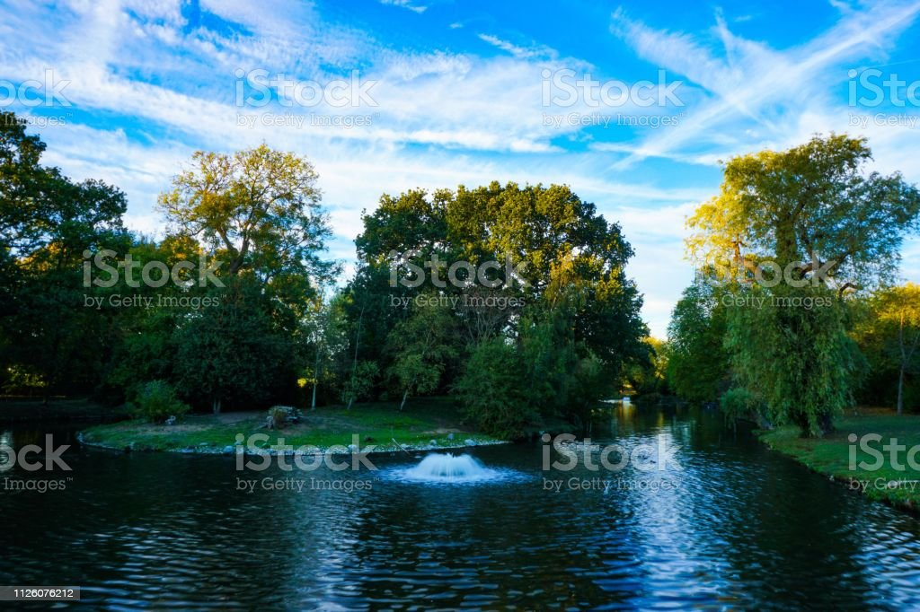 Water spout in London Regents Park lake at dusk stock photo
