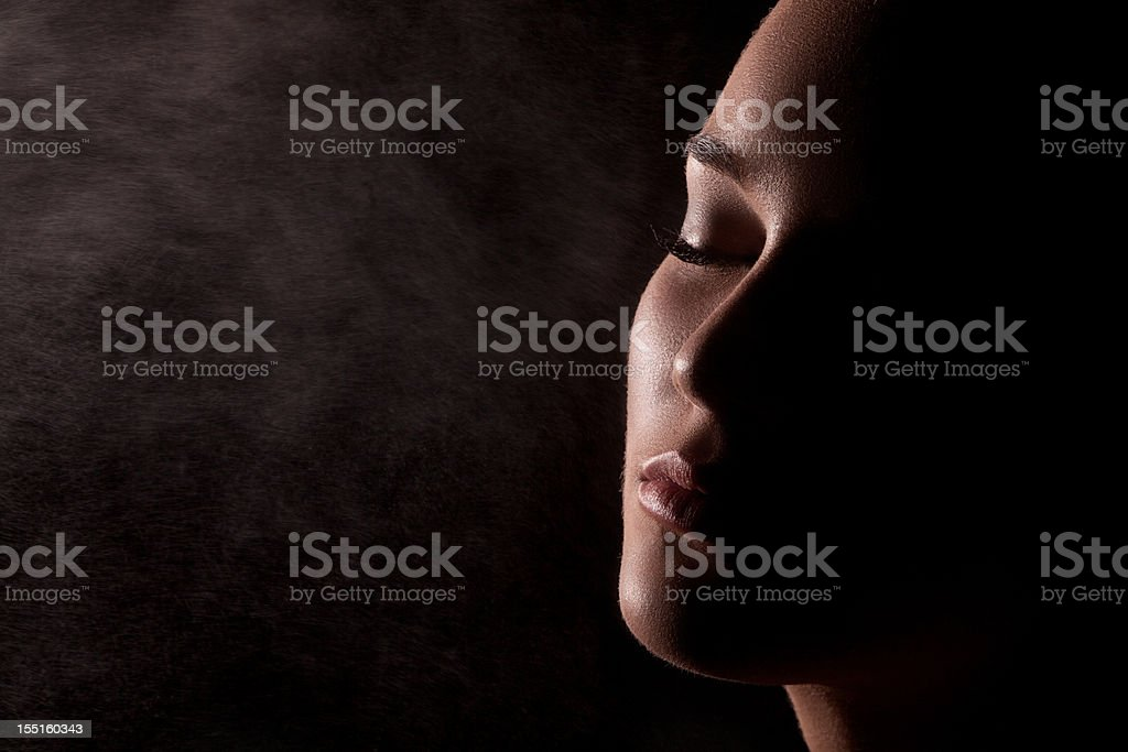 Water spray splashing on womans face over black background. Low stock photo
