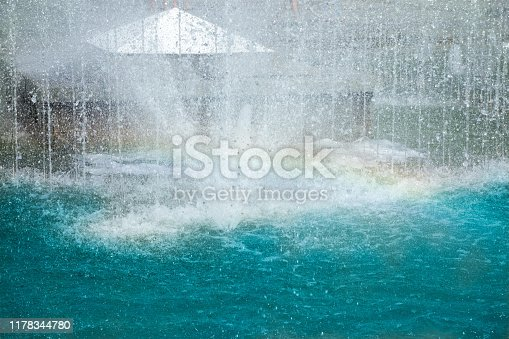 Water sprays and splashes of fountain in park or garden. Jets and drops of waterworks in summer day