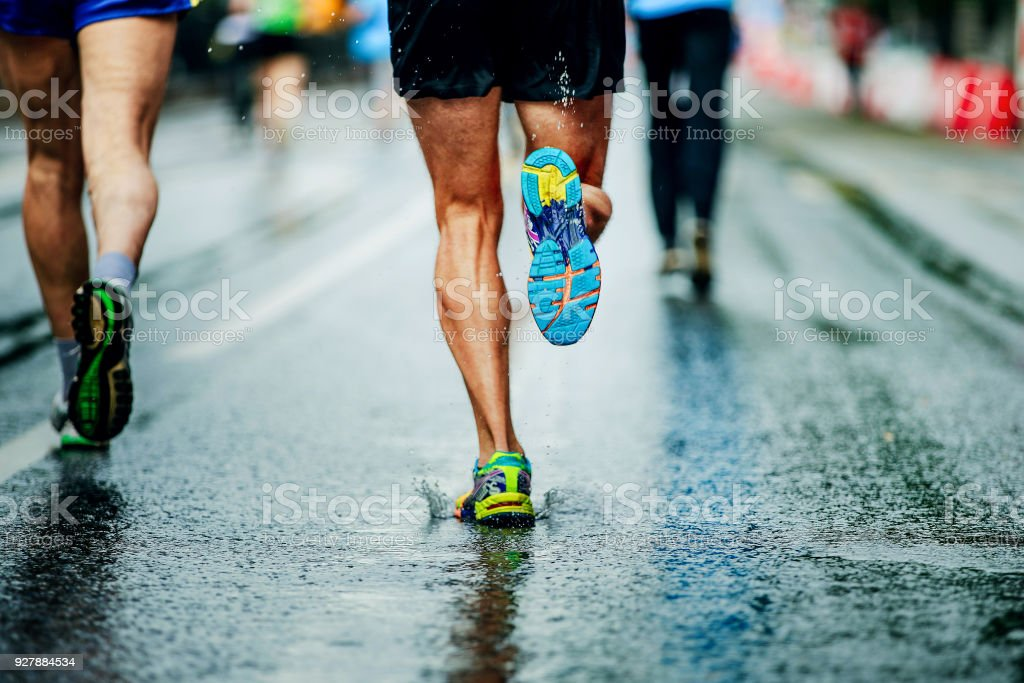 water sprays from under running shoes runner men stock photo