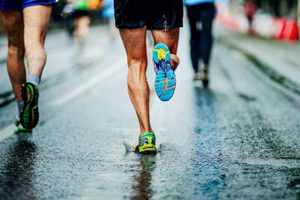 water sprays from under running shoes runner men - marathon stock photos and pictures