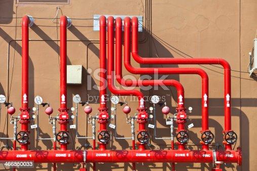 splinker alarm system, red water pipe, brown wall, outdoor
