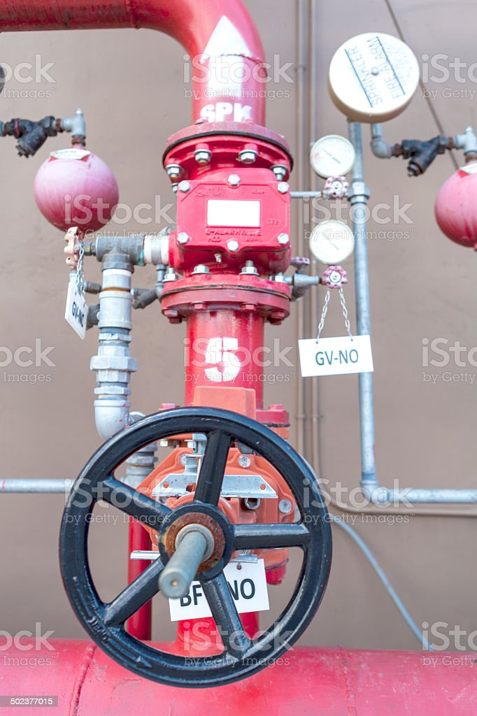 water sprinkler system control, fire fighting pipeline, red metal pipe stock photo