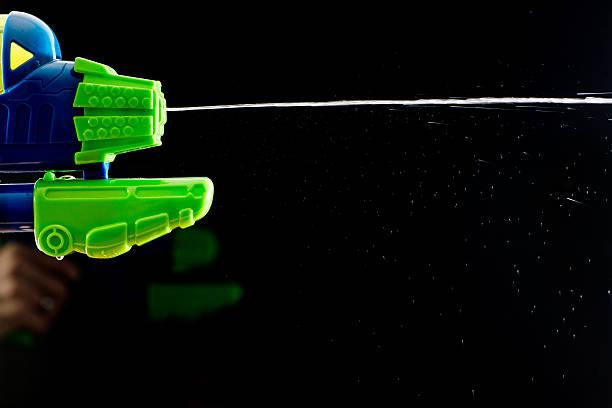 water Heraussprühen pistol gun shootinh Wasser auf Schwarz – Foto