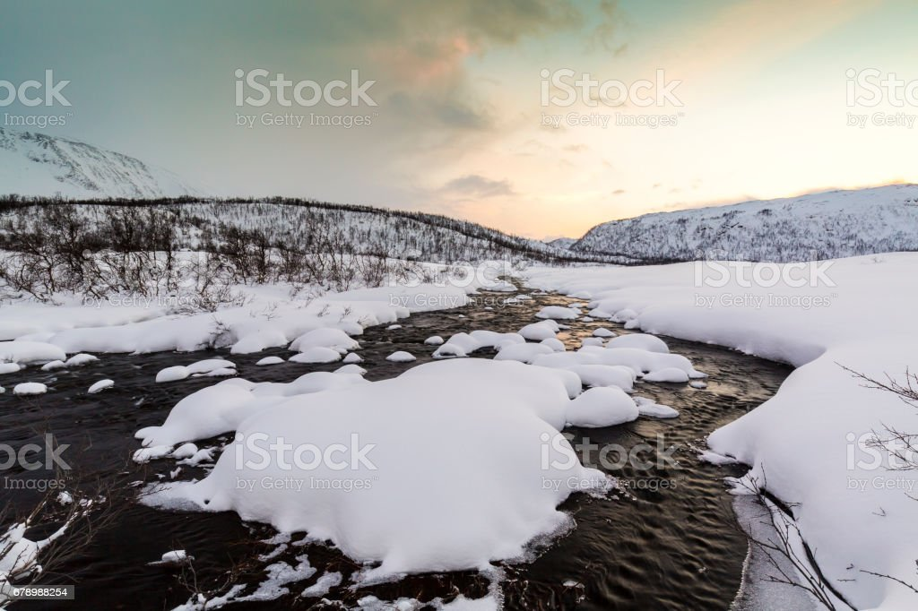 Water stream with rocks in a winter landscape in twilight. royalty-free stock photo