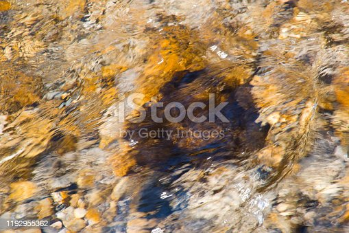 Water streaming fast over rocks in a riverbed in blurred motion