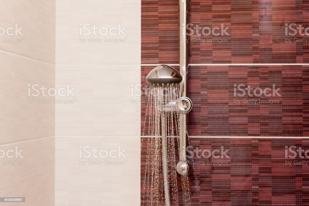 Water streams flow out of working shower head right down stock photo