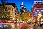 Long exposure stock photograph of Water street with the steam clock and the Vancouver Lookout in the background in Gastown, downtown Vancouver, British Columbia, Canada at twilight.