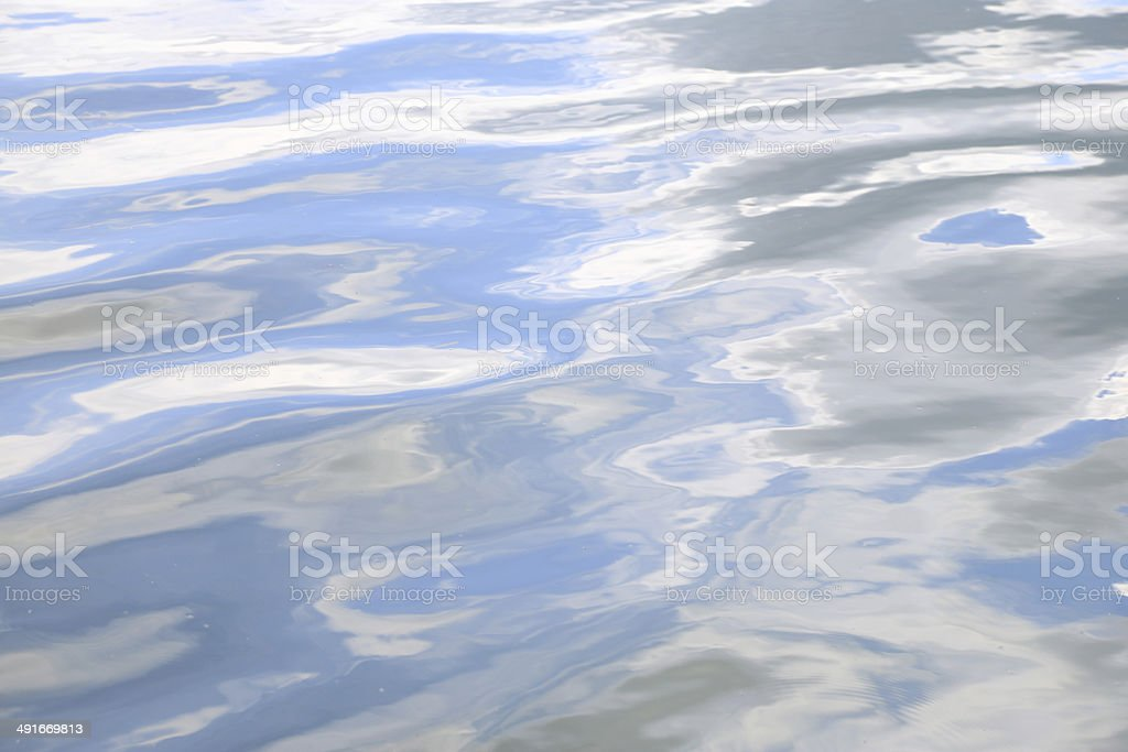 Water surface texture with soft ripples and sky reflection stock photo