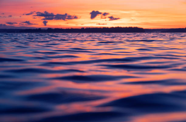 Water surface. View of a Sunset sky background. Dramatic gold sunset sky with evening sky clouds over the sea. View of a Crystal clear sea water texture. Landscape. Small waves. Water reflection stock photo