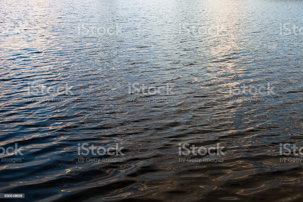 Water surface with ripples and sunrays reflections stock photo