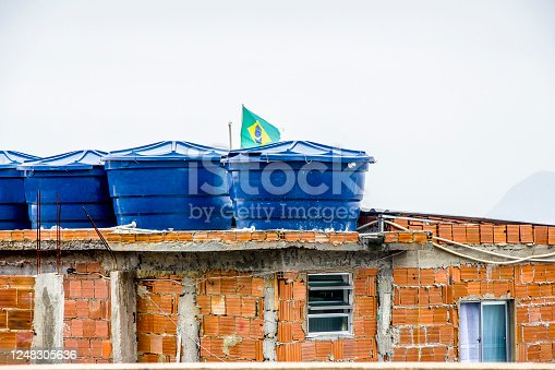 water tank on top of a house with the flag of brazil on the hill of cantagalo in Rio de Janeiro