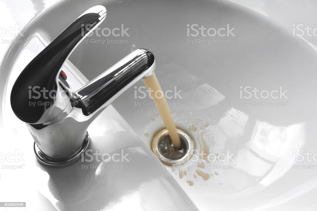 Water Tap With Running Dirty Muddy Water in a Sink stock photo