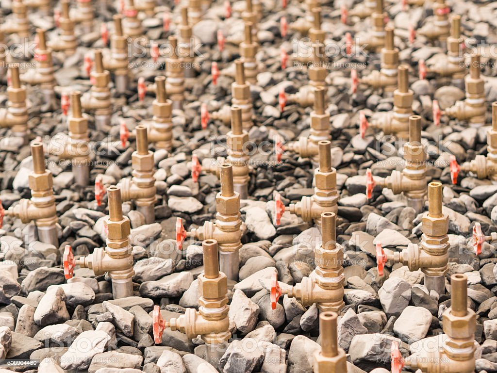 Water taps of fountain court, closeup among gravel. stock photo