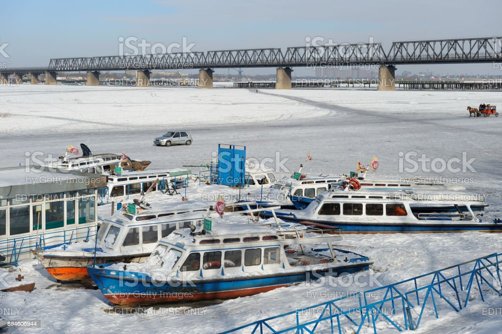Water taxi boats trapped on frozen Songhua river. Cars traffic in background. stock photo