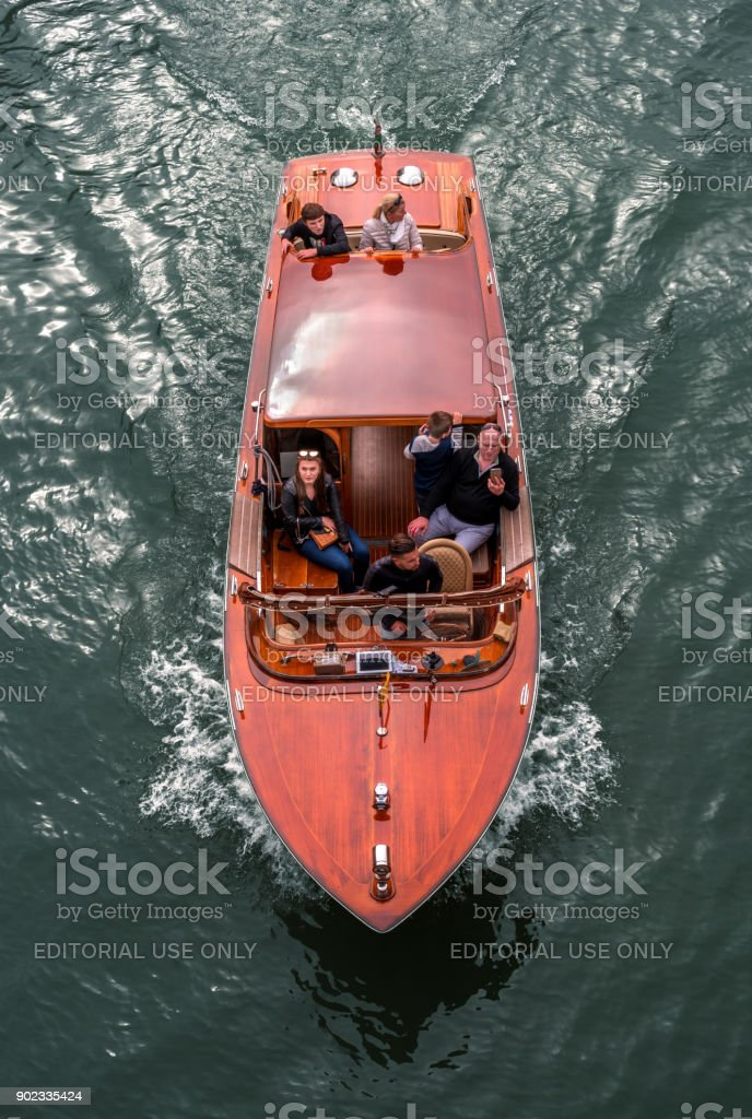 Venice, Italy - October 13, 2017: Water taxi in the Grand Canal. Tourists visiting the sights. Family from adults and children. stock photo