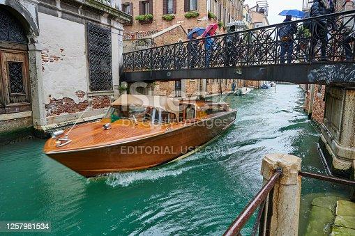 Venice, Italy - November 24, 2019: a water taxi transporting tourists sailing under Bridge De La Bergama in S. Croce Quarter.