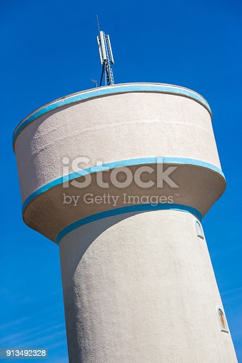 Closeup on water tower with a beautiful blue sky in the background