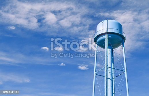 A city water tower set against a blue sky