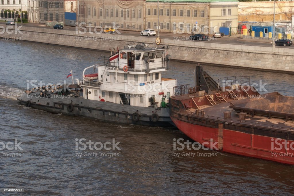 Water transport. River boat tow pusher in the canals of the Moscow river against the backdrop of the capital of Russia stock photo
