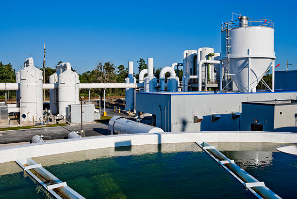 Water Treatment Facility with Water Tank in Foreground Water Treatment Facility sewage treatment plant stock pictures, royalty-free photos & images
