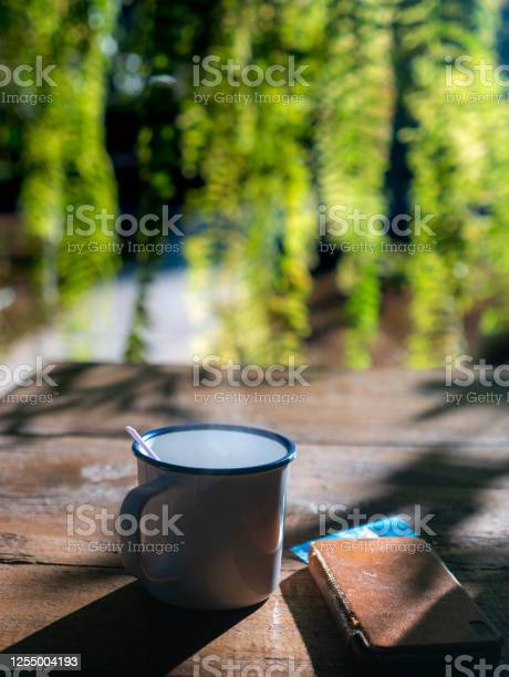 Photo of Water Vapor on Top of  The Coffee Cup and The Old Mobile Phone on The Right Side