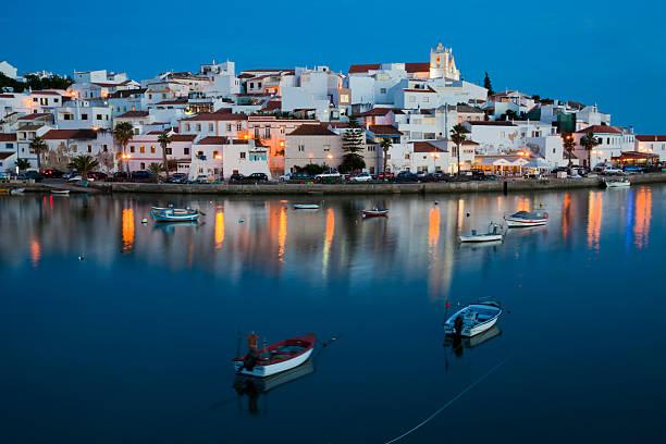 Water view of illuminated cityscape of Ferragudo in Algarve stock photo