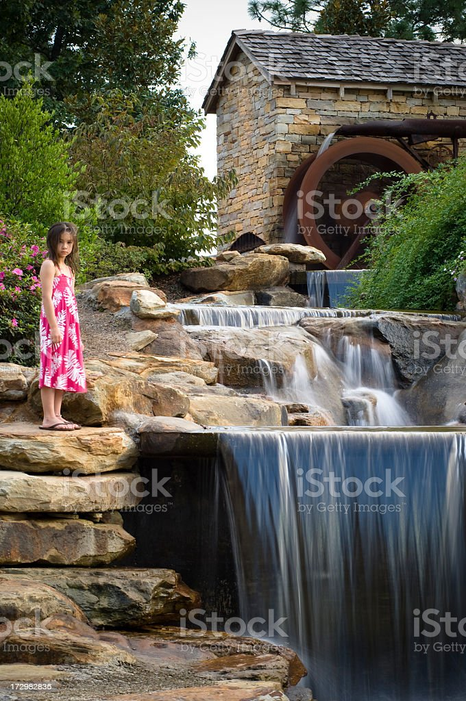 water wheel girl by cascading creek in landscaping stock photo